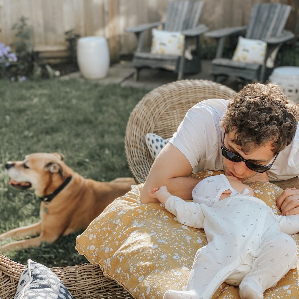 A father and his baby sitting on outdoor furiture in a backyard with their dog