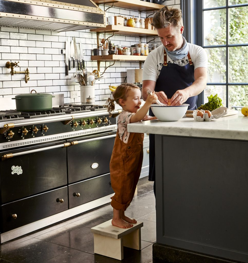 A child using a franklin + emily step stool to help cook