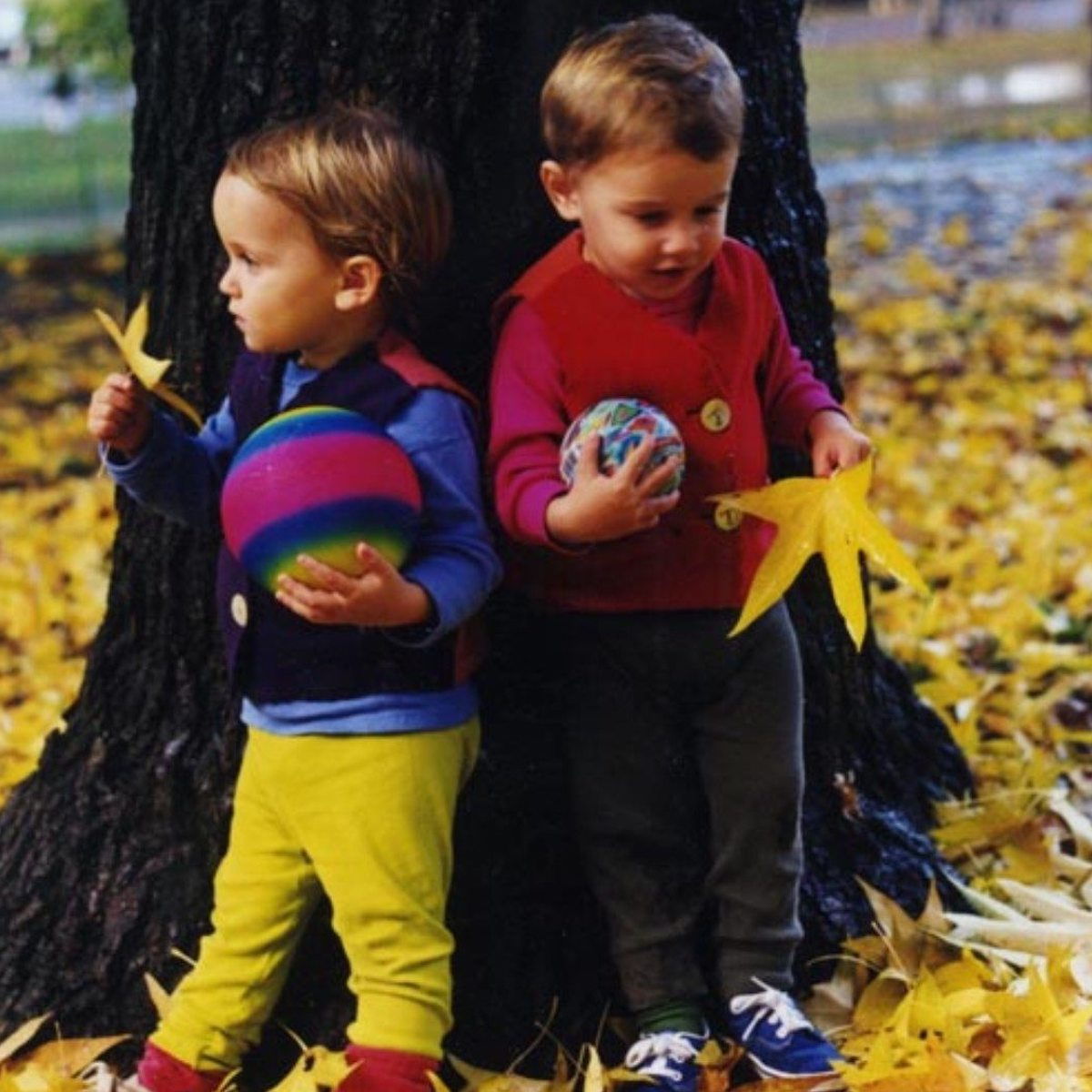 Two children playing outside by a tree with fall leaves and eeBoo toys