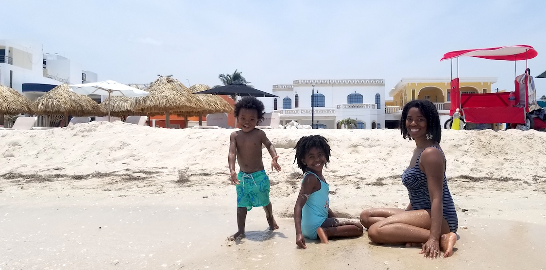 Travel Blogger, Ashley Corinne, and her two children on a beach in Mexico