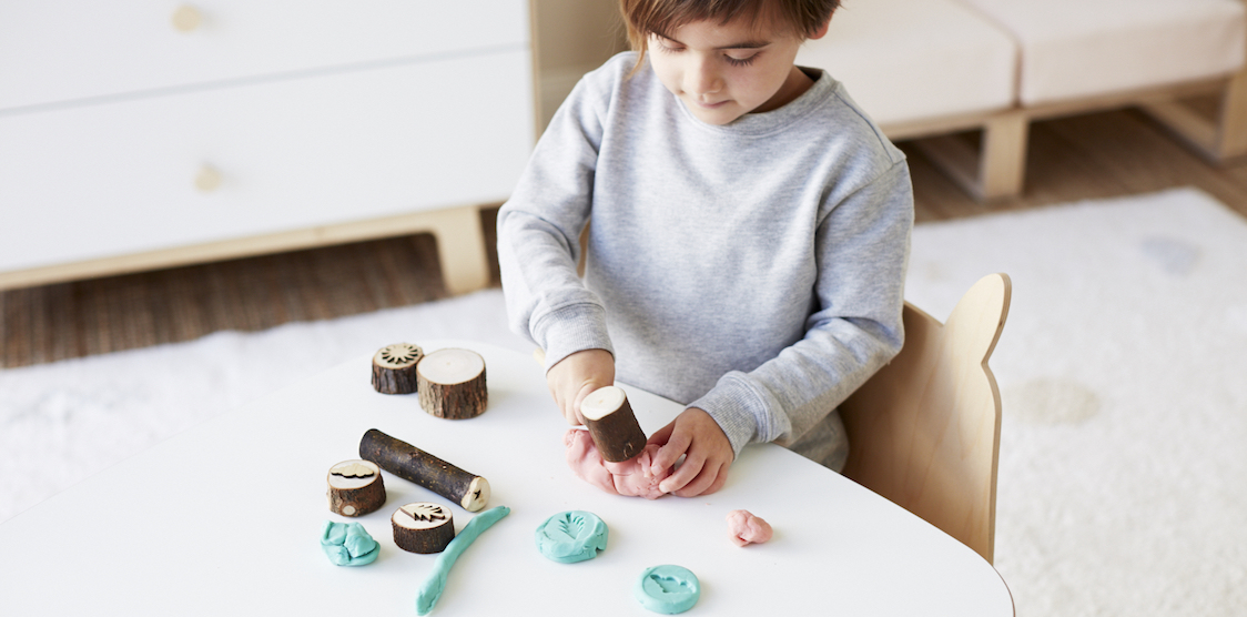 A little girl playing with the Let Them Play Dough Kit and Dough Parlour's non-toxic play dough.