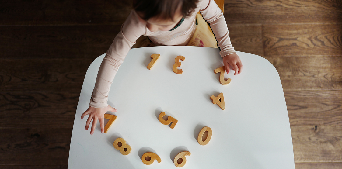 child playing with wooden number blocks