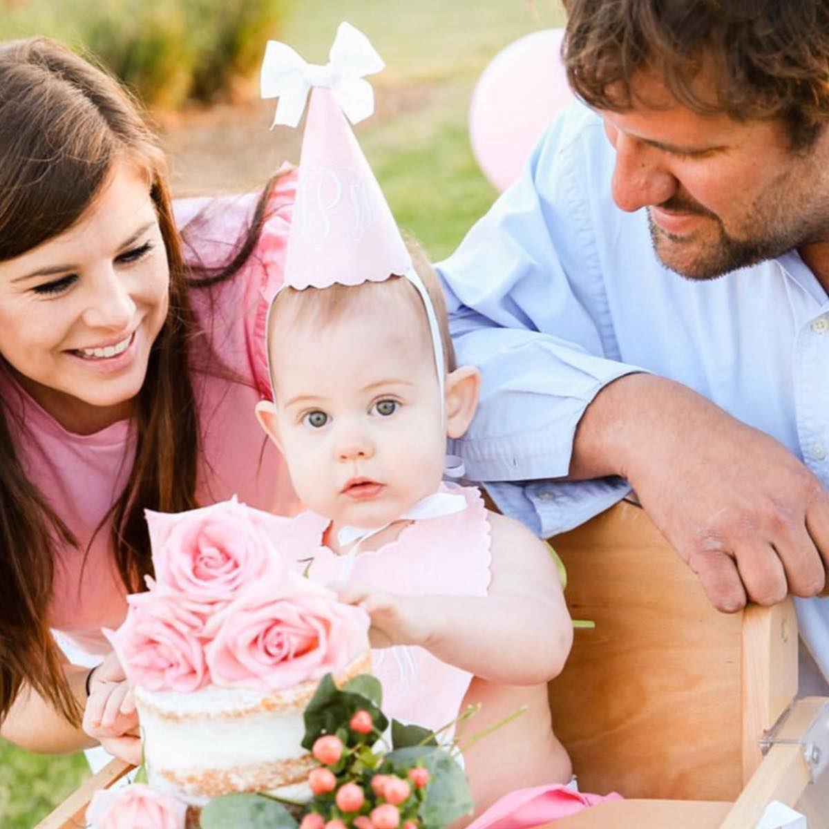 two parents and their child celebrating a birthday with a rose birthday cake