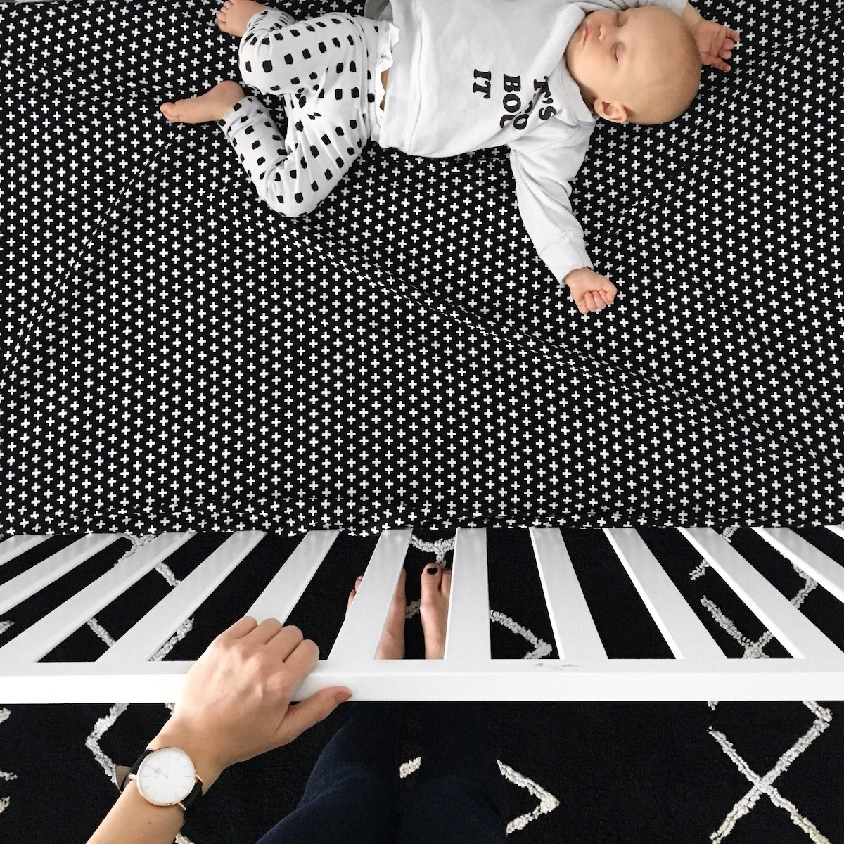 an infant sleeping in a crib with an Olli + Lime fitted crib sheet