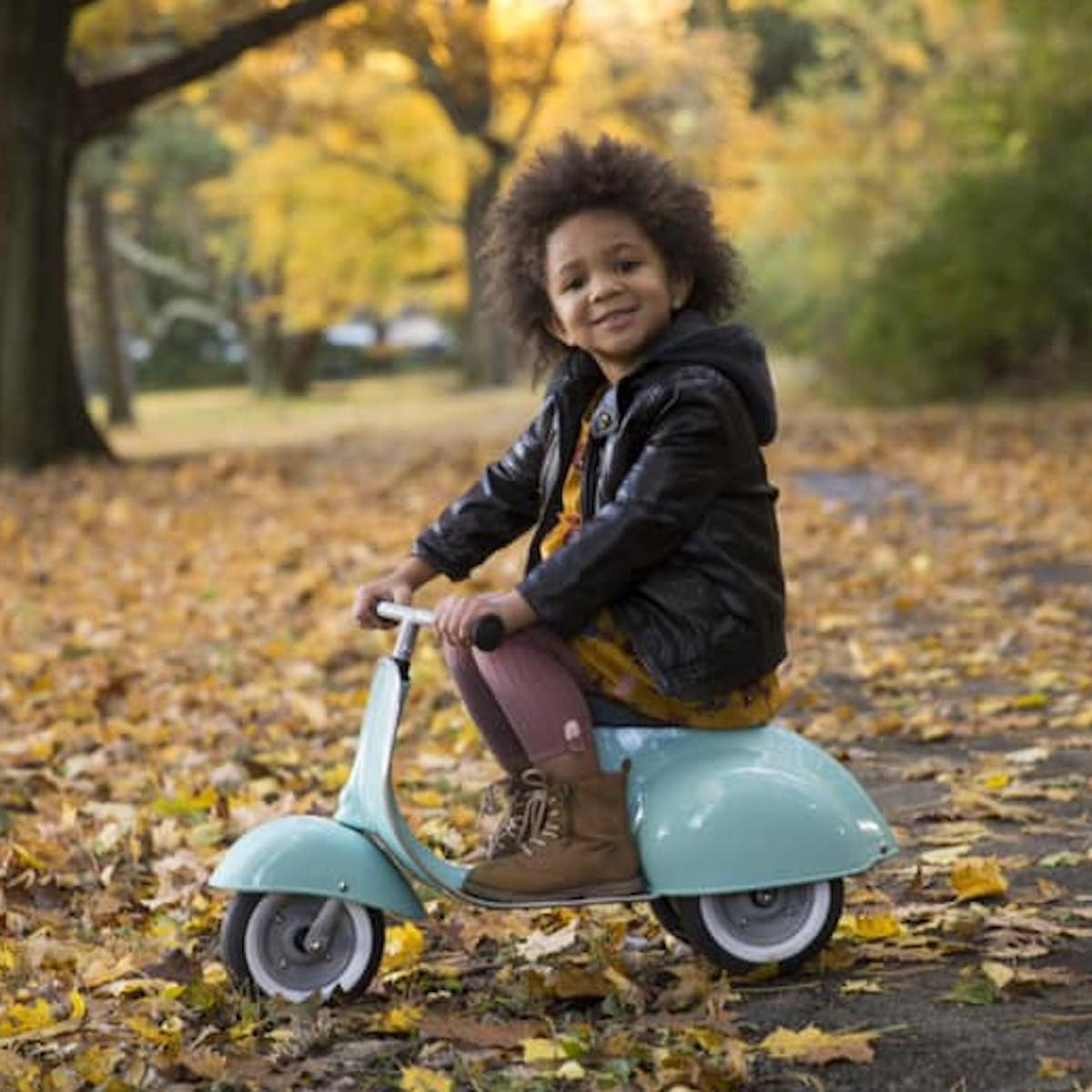 Young child riding an Ambosstoys scooter in the fall foliage