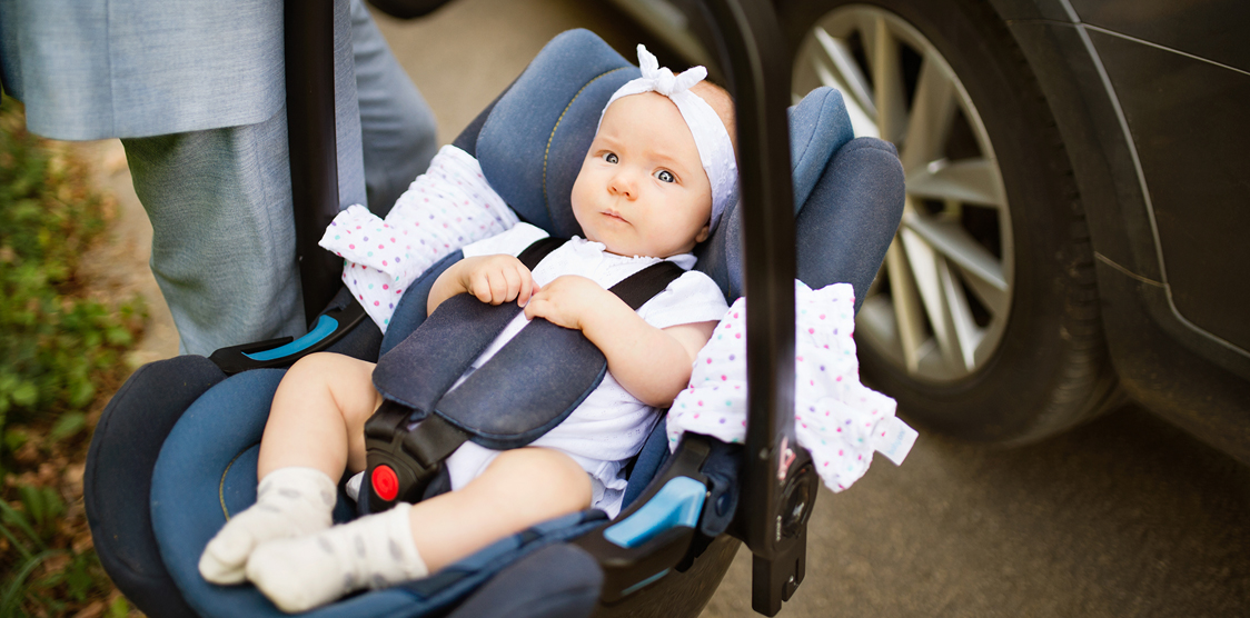 Young baby being carried in a car seat