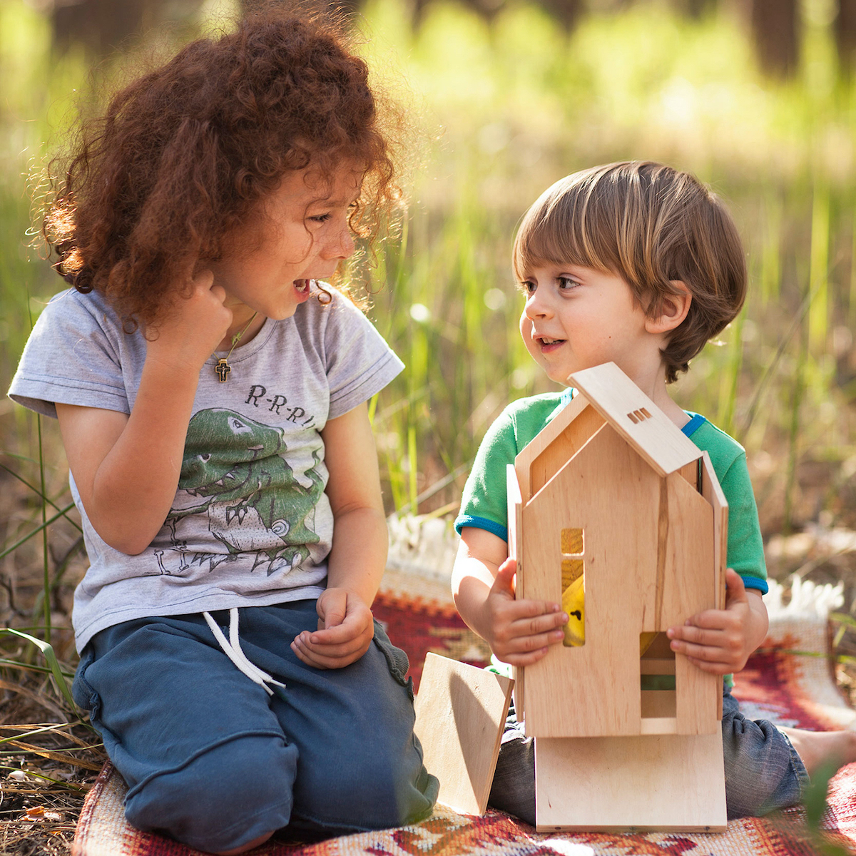 Two children playing with a wooden Babai dollhouse on a picnic blanket