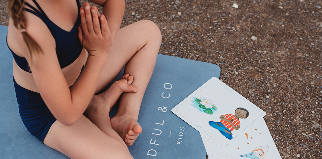 A child doing yoga poses with the Mindful & Co Kids Yoga Flash Cards