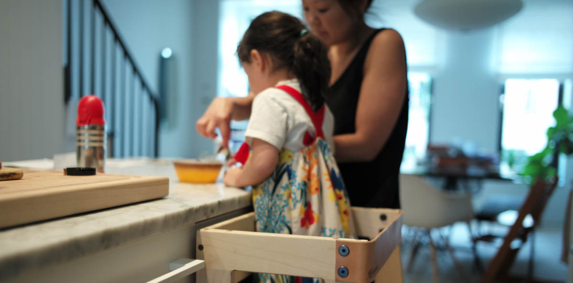 child using a learning tower in the kitchen