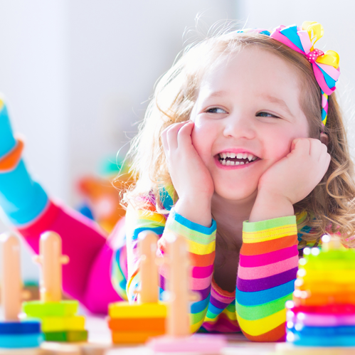 Little girl wearing a rainbow shirt lying down next to colorful stacking toys