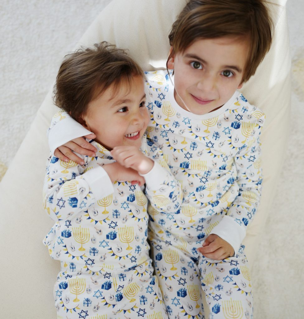 Two girls wearing HART + LAND organic pima cotton PJs in a hanukkah print