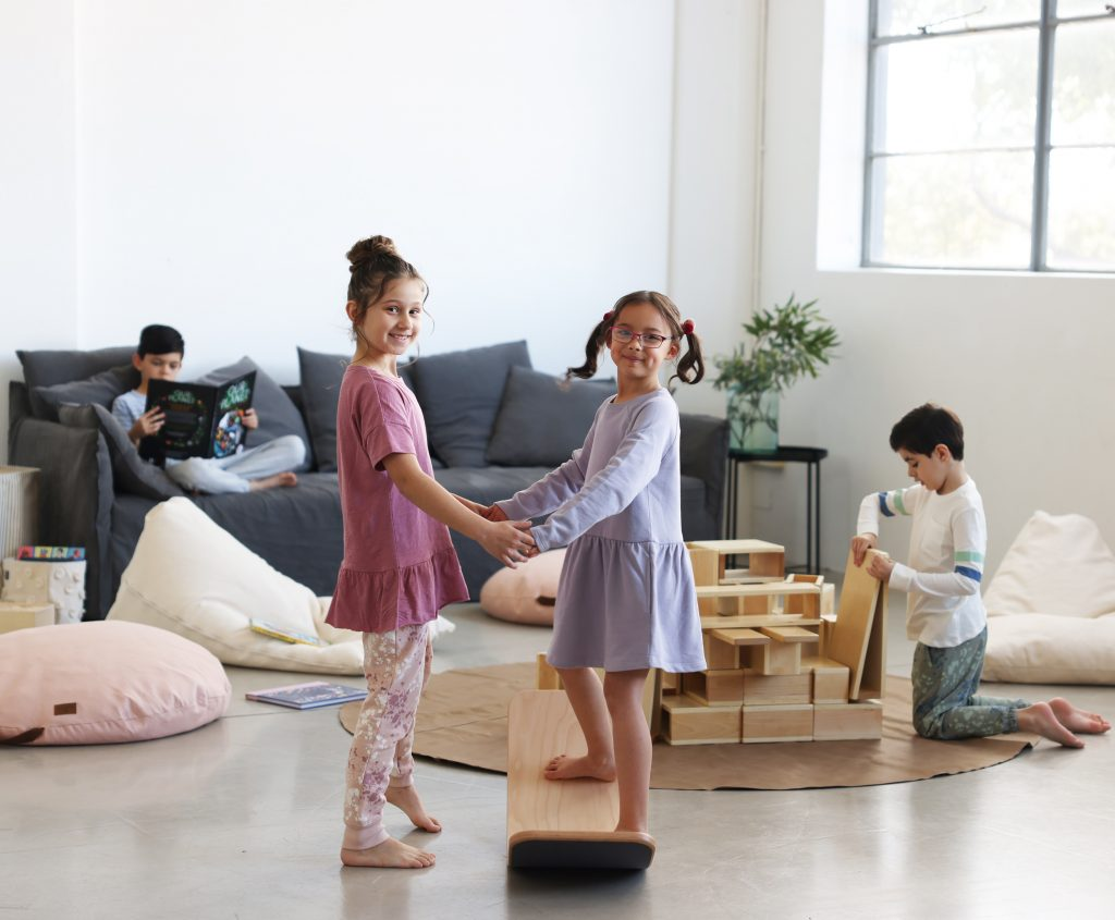 Two girls playing on a Wobbel board while wearing HART + LAND organic cotton basics