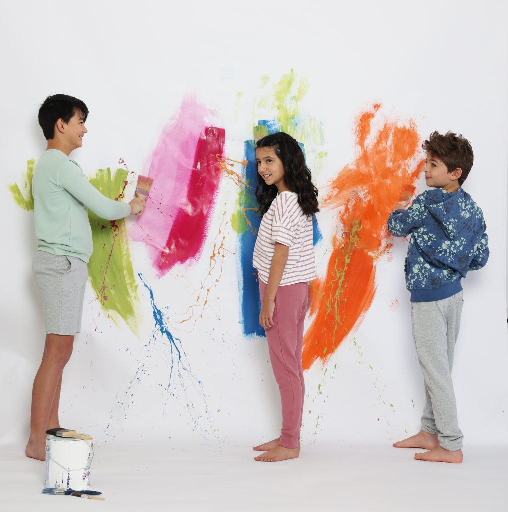 A group of kids wearing HART + LAND Organic Cotton basics while painting
