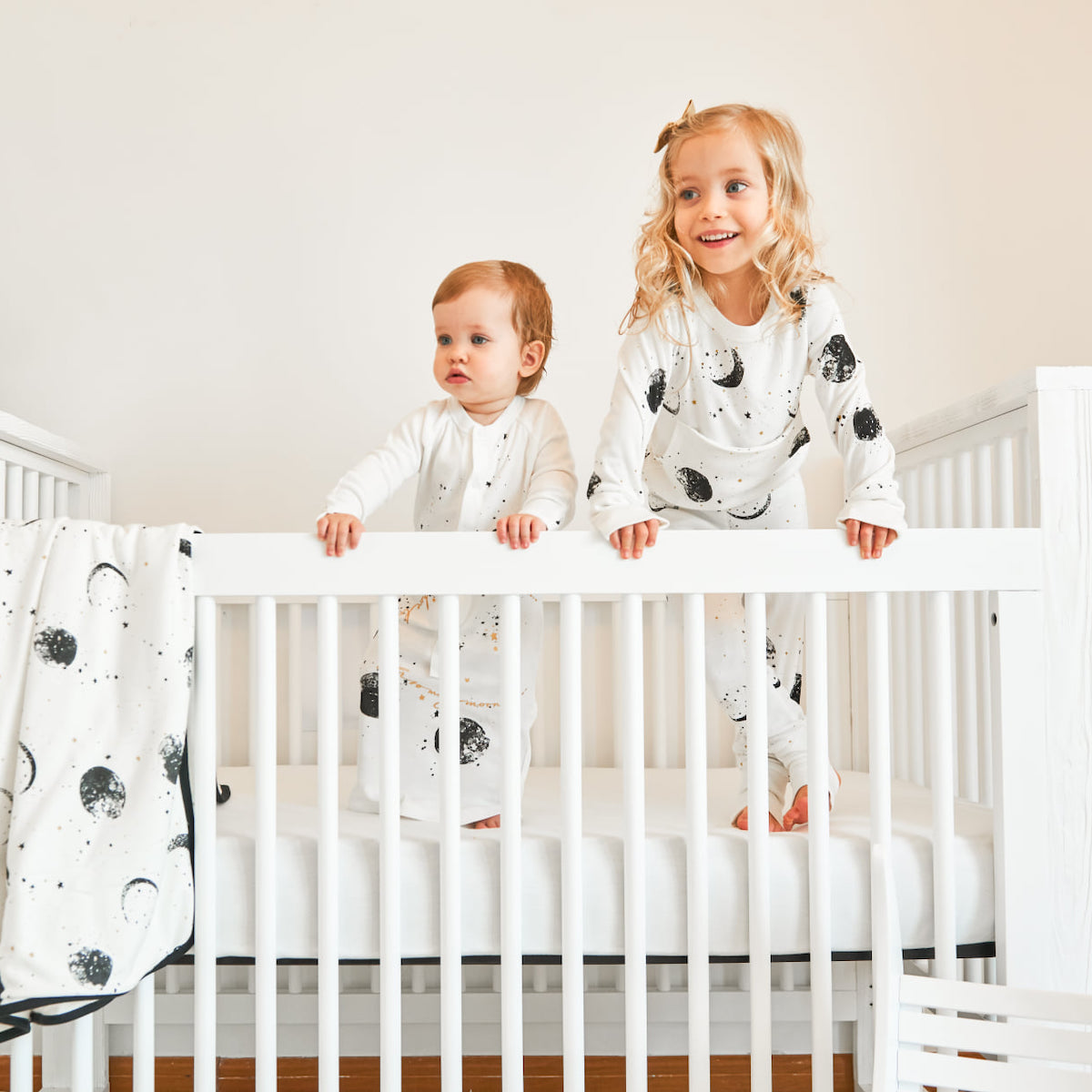 A baby and a young girl in a white Millk Street Baby crib.
