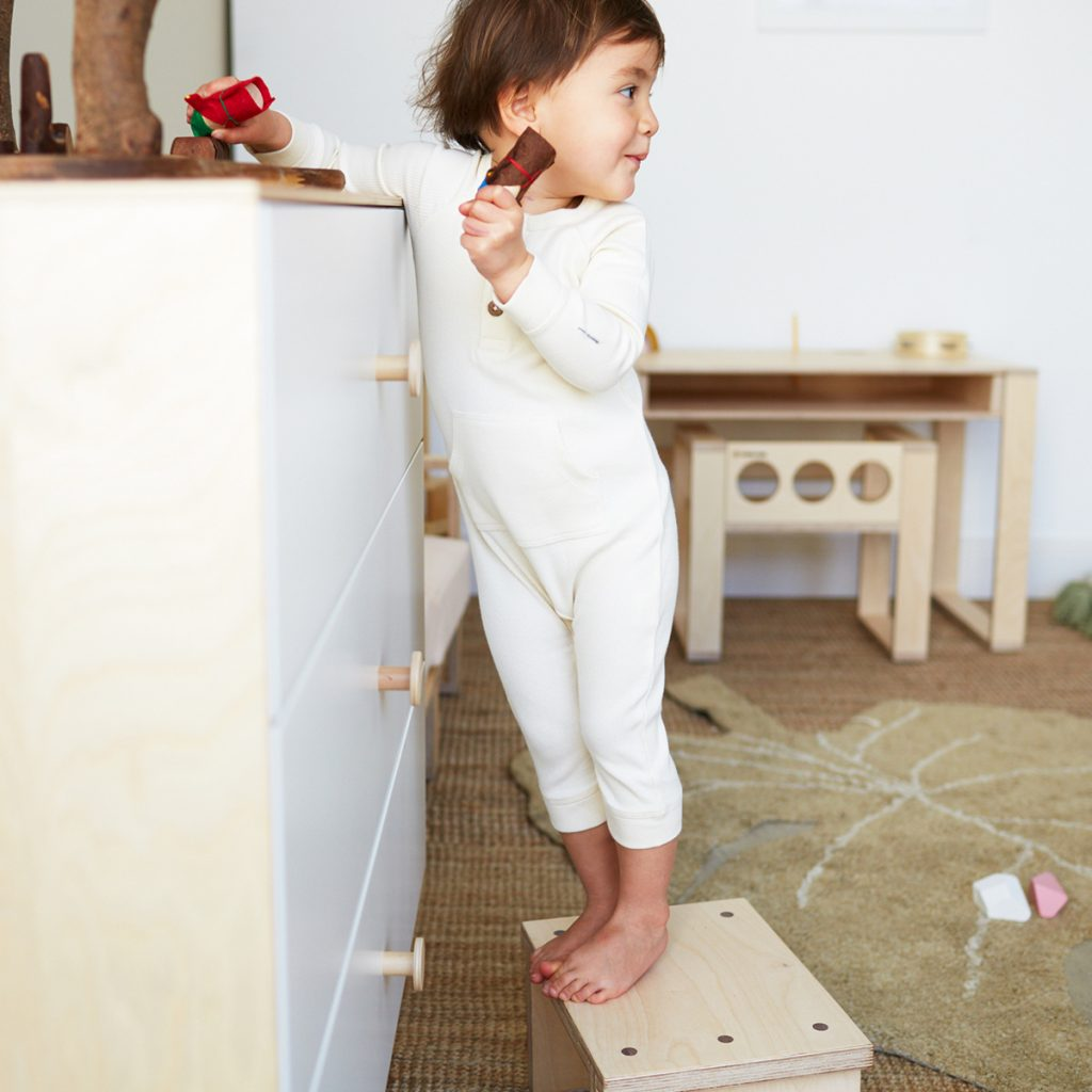 A little girl wearing the HART + LAND organic cotton ribbed romper while playing in her nursery