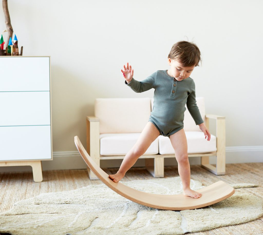 A little girl wearing HART + LAND organic cotton rib basics while playing on a wobbel