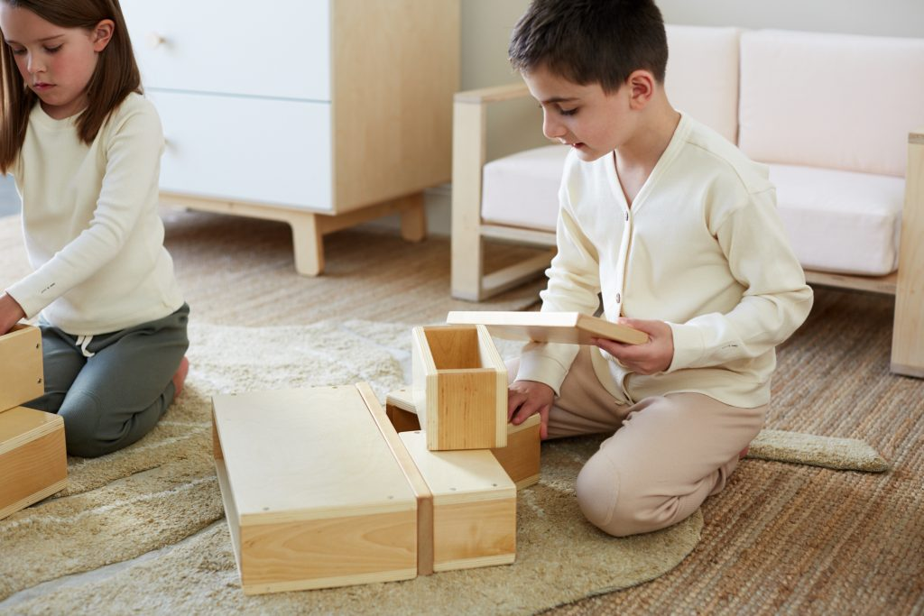 Two kids wearing HART + LAND Organic Cotton Rib basics while playing with Guidecraft hollow blocks