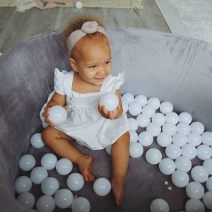 a little girl playing in a balu organics ball pit