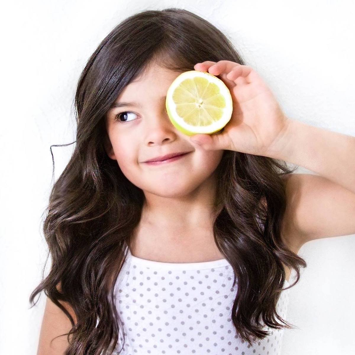 Little girl holding up a half of a lemon wearing Dott Child basics