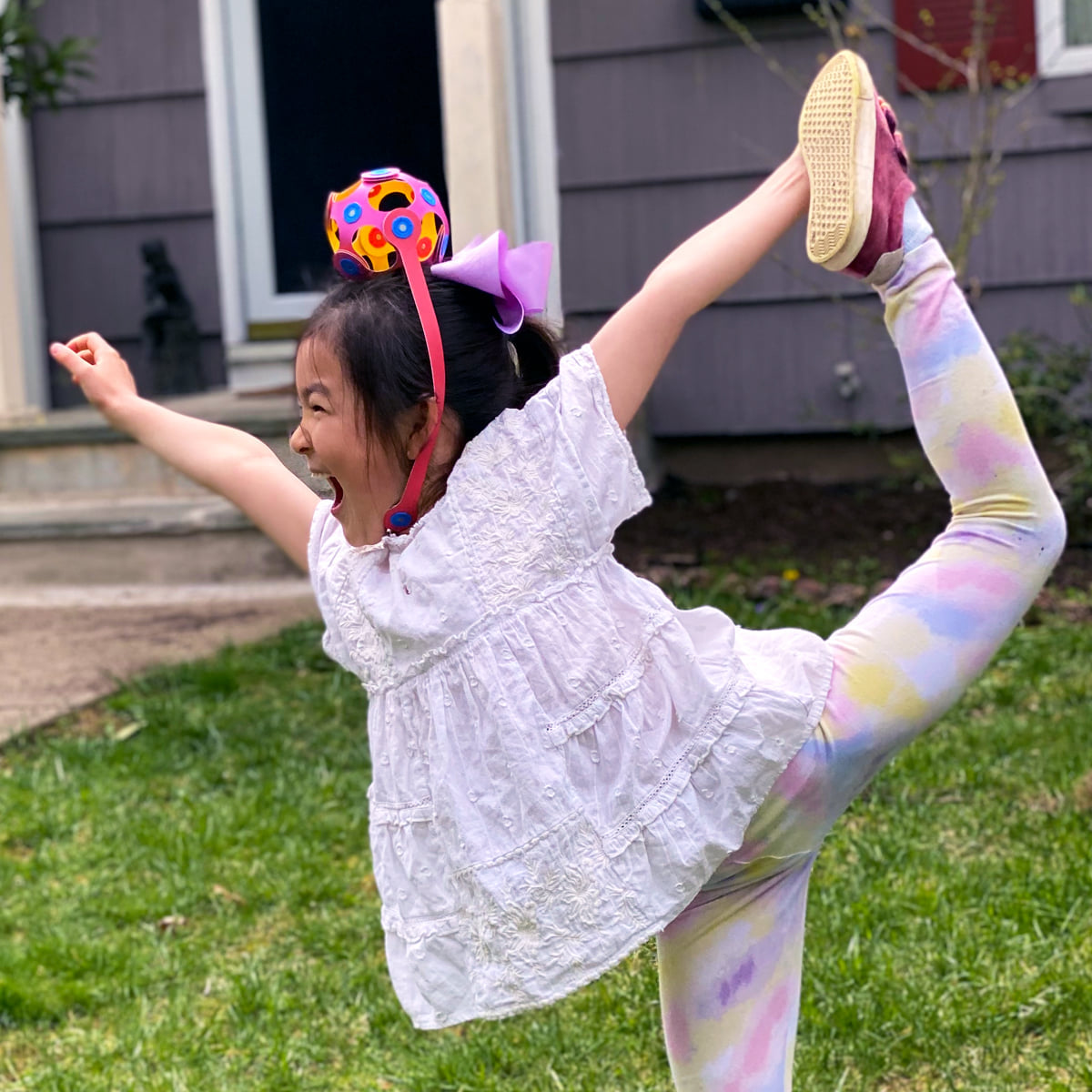 A little girl doing a Scorpion cheerleading pose in a backyard with a Clixo creation on her head