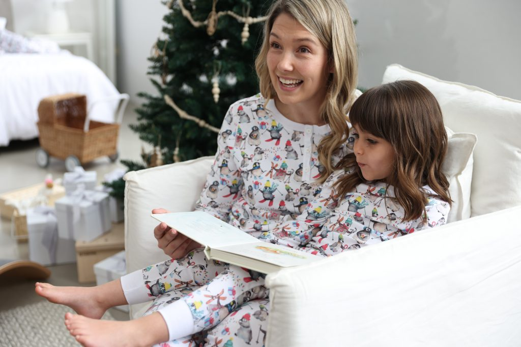 A woman and her daughter on Christmas day wearing HART + LAND winter penguin print pima cotton pjs