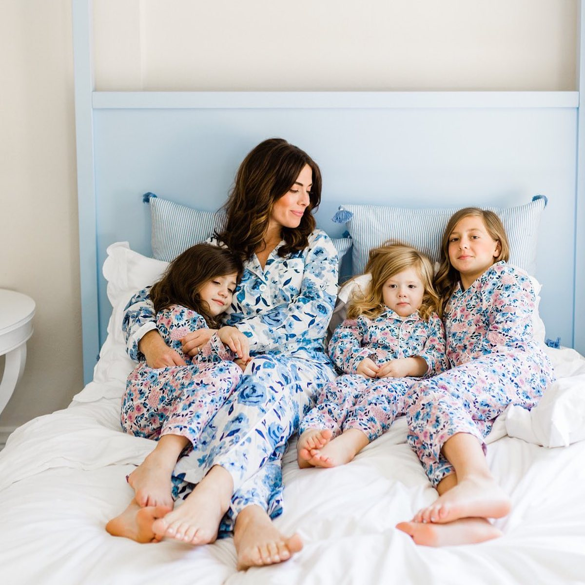 Designer Caitlin Wilson and her children in a blue Cait Kids bed