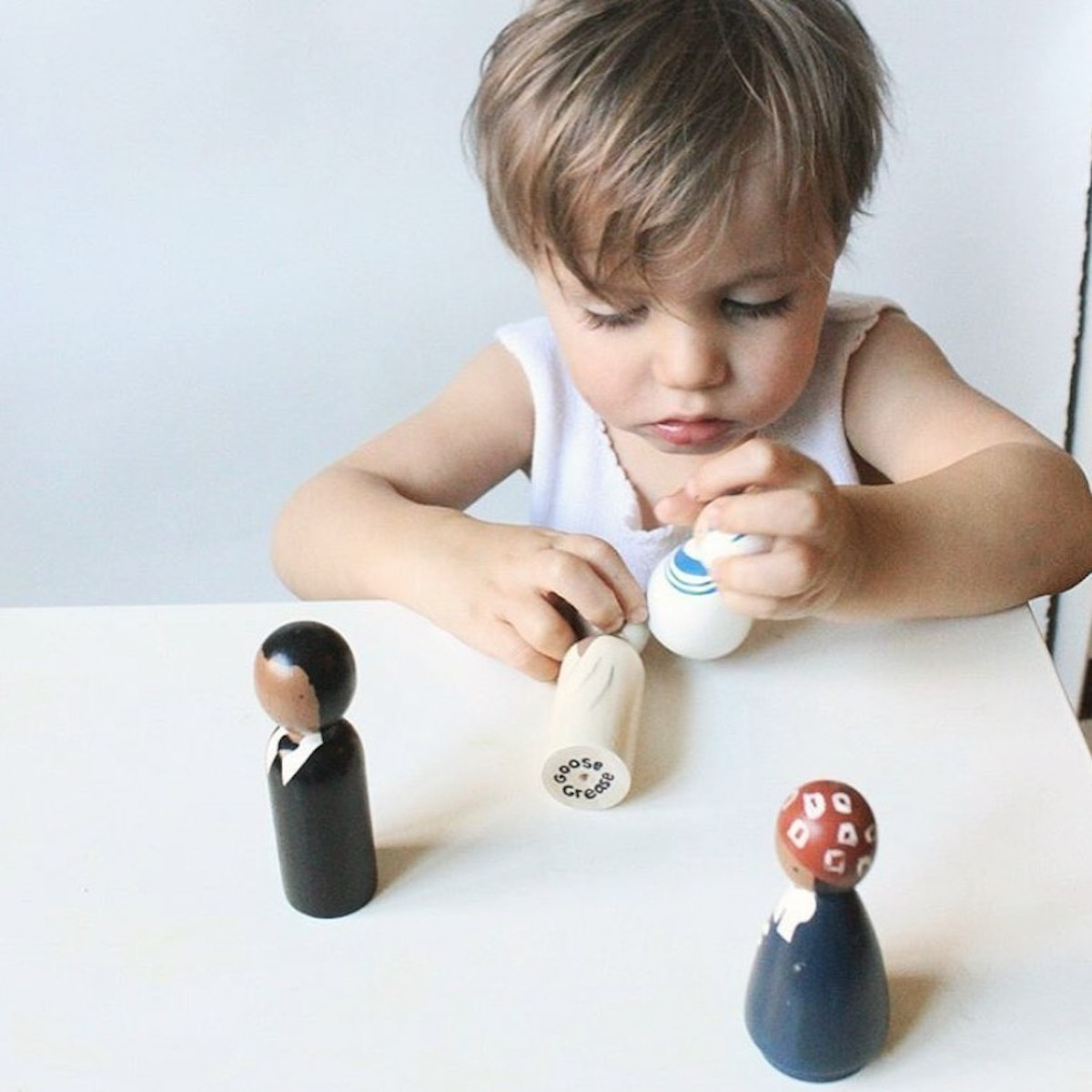A toddler playing with Goose Grease handmade peg dolls