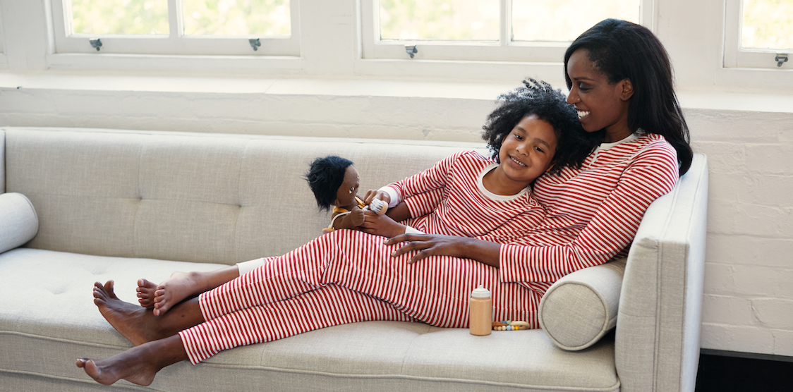 A woman and her child wearing matching HART + LAND red stripe pajamas while lying on a couch