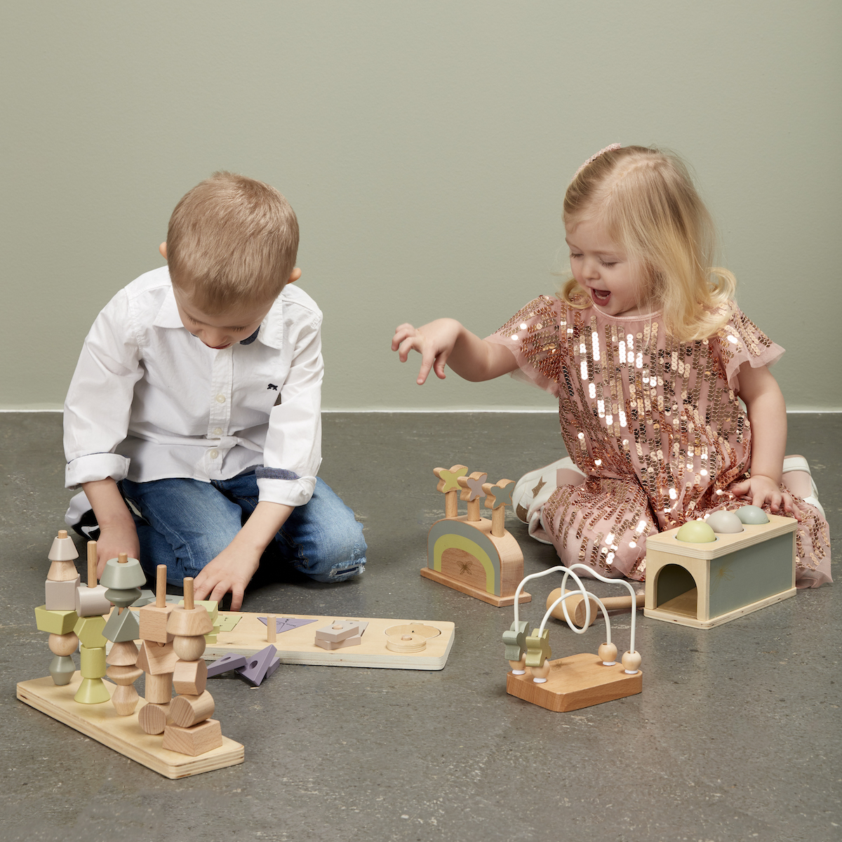 Two children playing on the floor with by ASTRUP wooden toys