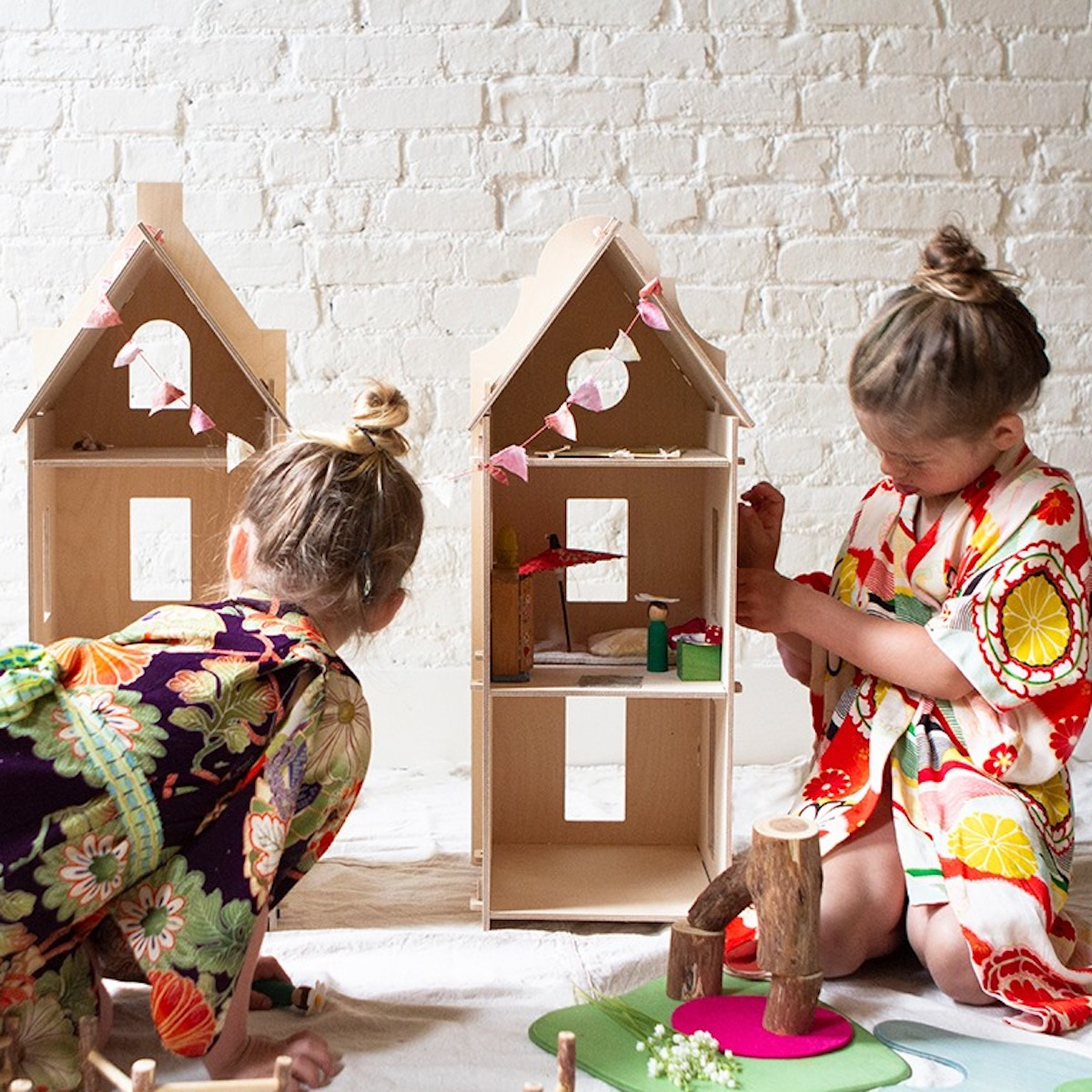 Two little girls wearing kimonos and playing on the floor with a Maquette Kids dollhouse