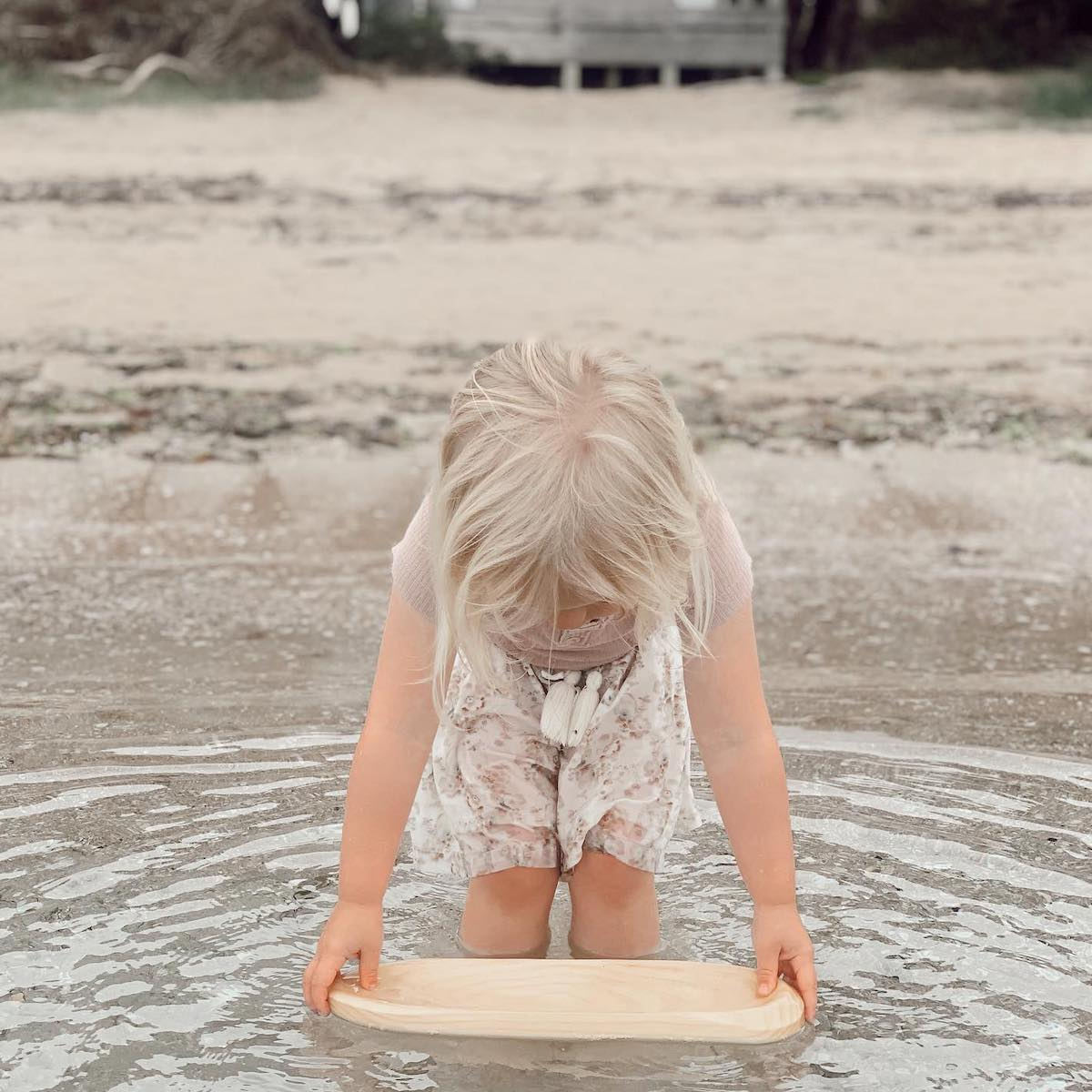Young child using an Explore Nook open-ended water toy to play at the beach.