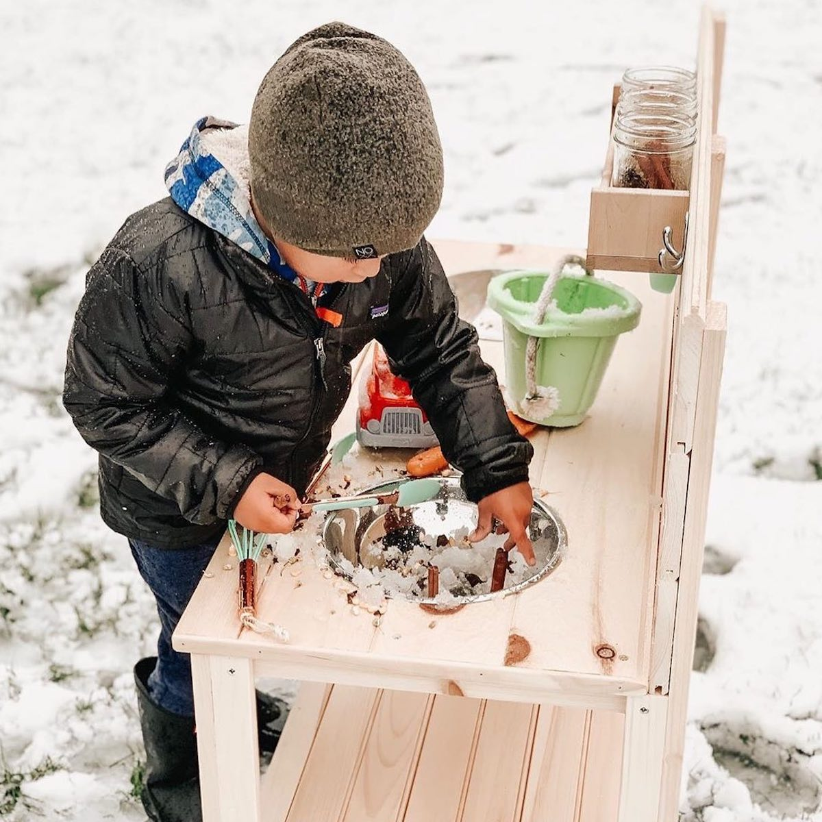 A little boy playing with The Monarch Studio mud kitchen outside in the snow