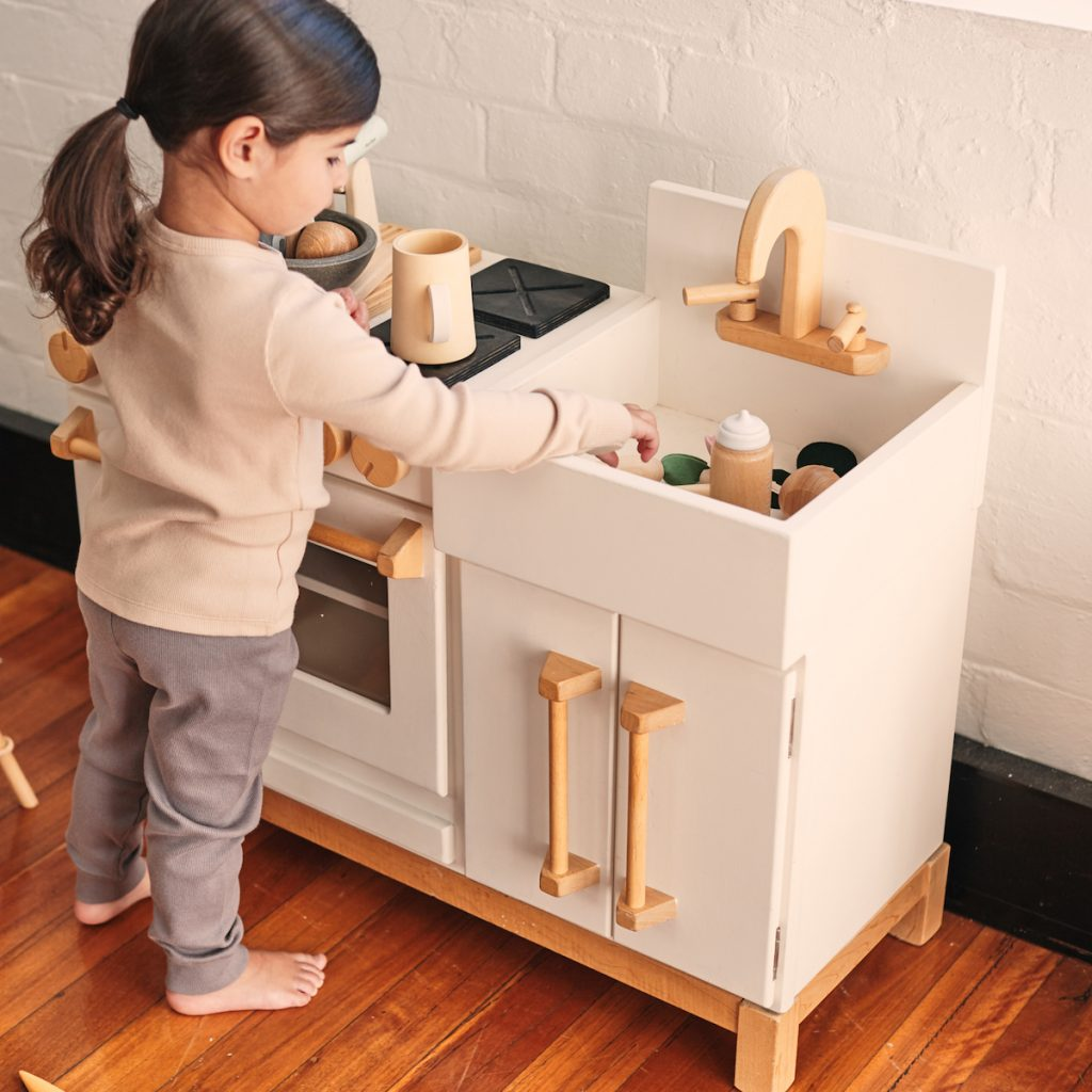 A kid playing with a Milton & Goose play kitchen