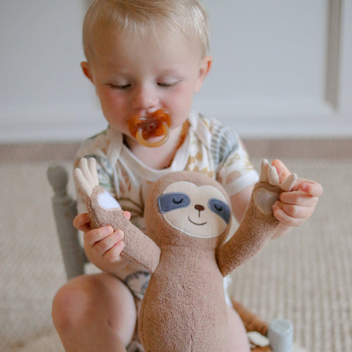 A toddler with a pacifier sitting in a rocking chair and holding an Apple Park sloth plush toy