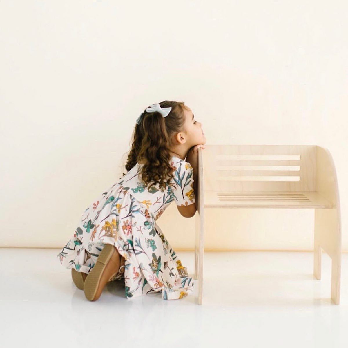 A young girl resting her chin on a Wit Design chair