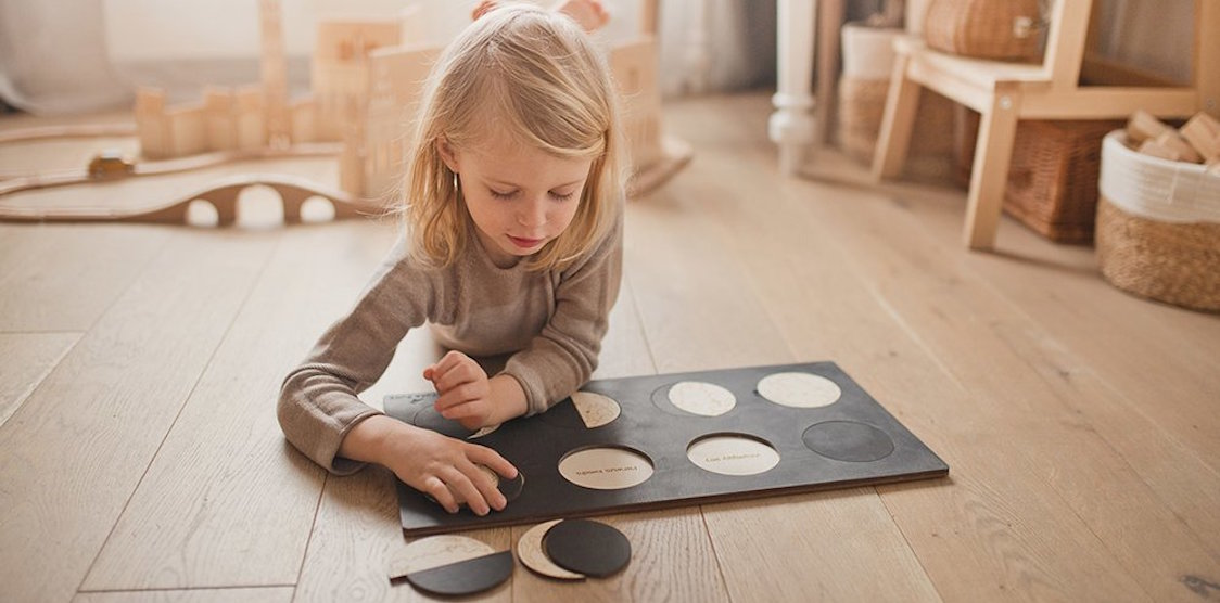 A child playing with the Stuka Puka Lunar Phases Wooden Puzzle