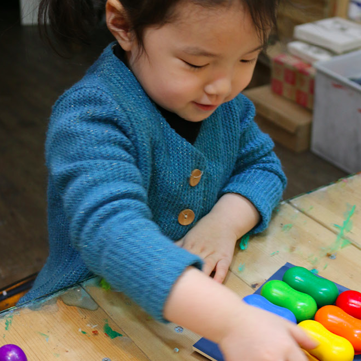 A young girl playing with Goober Crayons peanut crayons at an arts and crafts table
