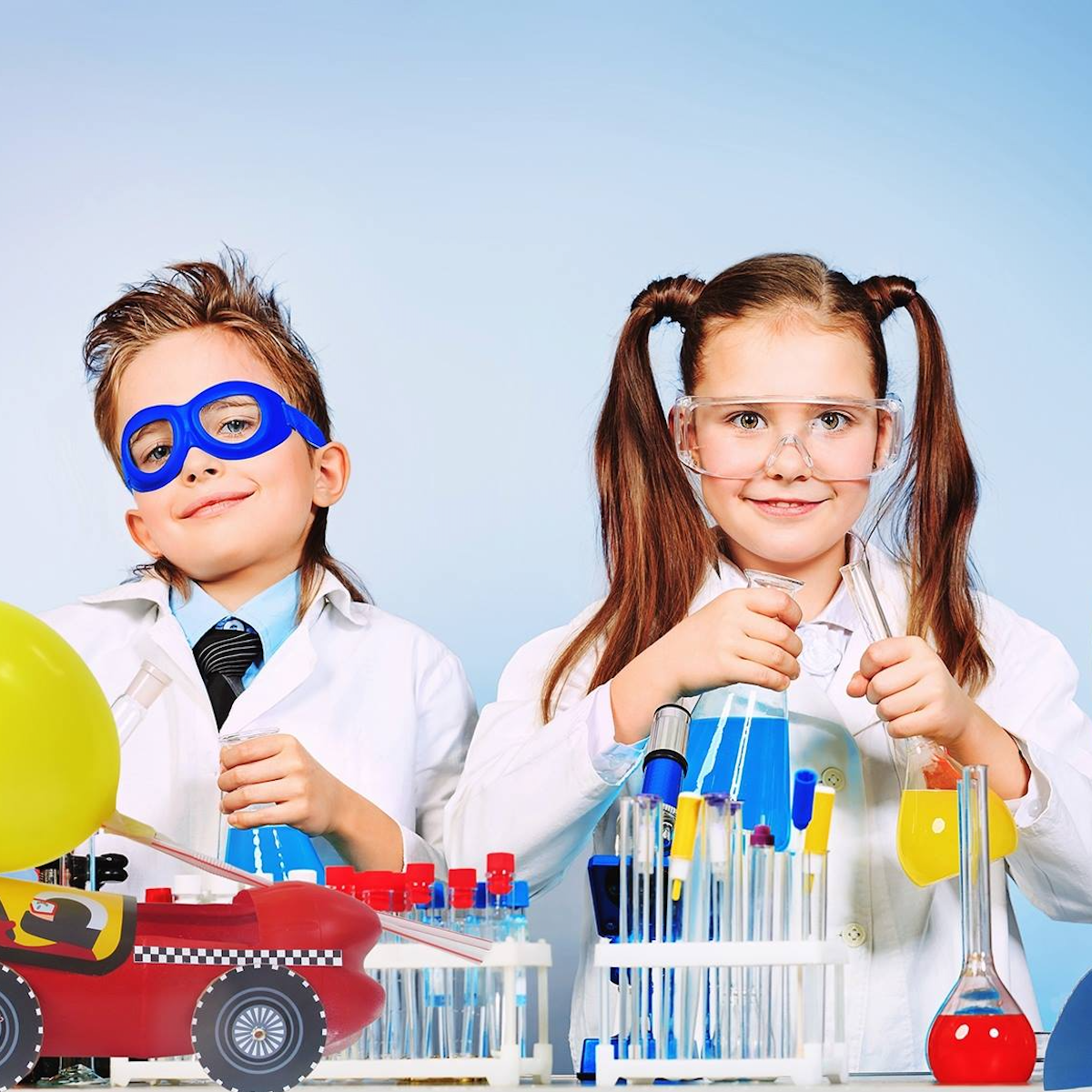 Two children wearing lab coats and playing with a Re-Cycle-Me science activity box