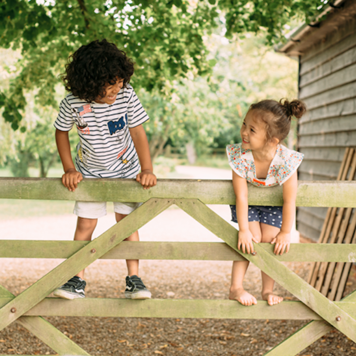 Two children playing o a wooden fence outside.