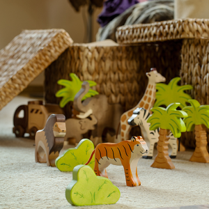 Wooden Holztiger animal figureines on a living room floor with a wicker basket in the background