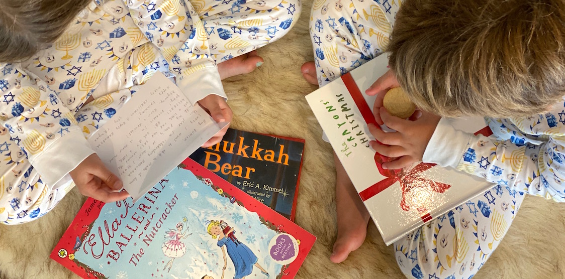 Two kids wearing HART + LAND Hanukkah PJs and reading the crayons' christmas book