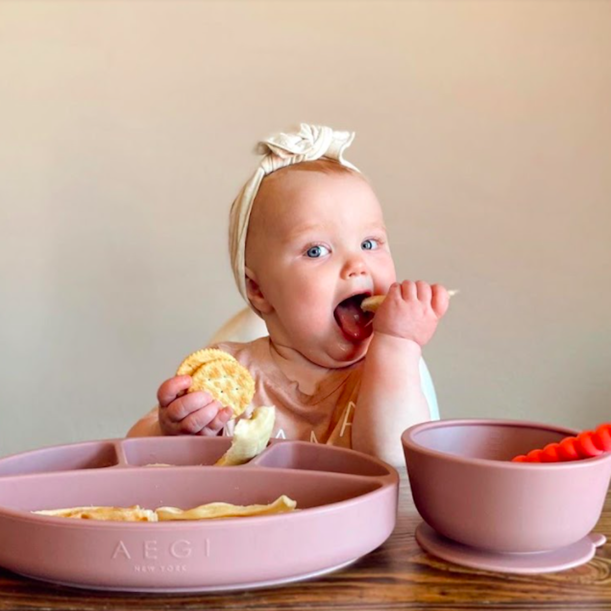 An infant in a highchair with Aegi silicone dinnerware and holding crackers