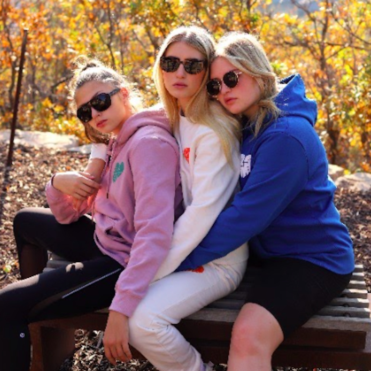 Three women wearing 1,2,3 Ciao hoodies sitting on a bench in a park amongst fall foliage