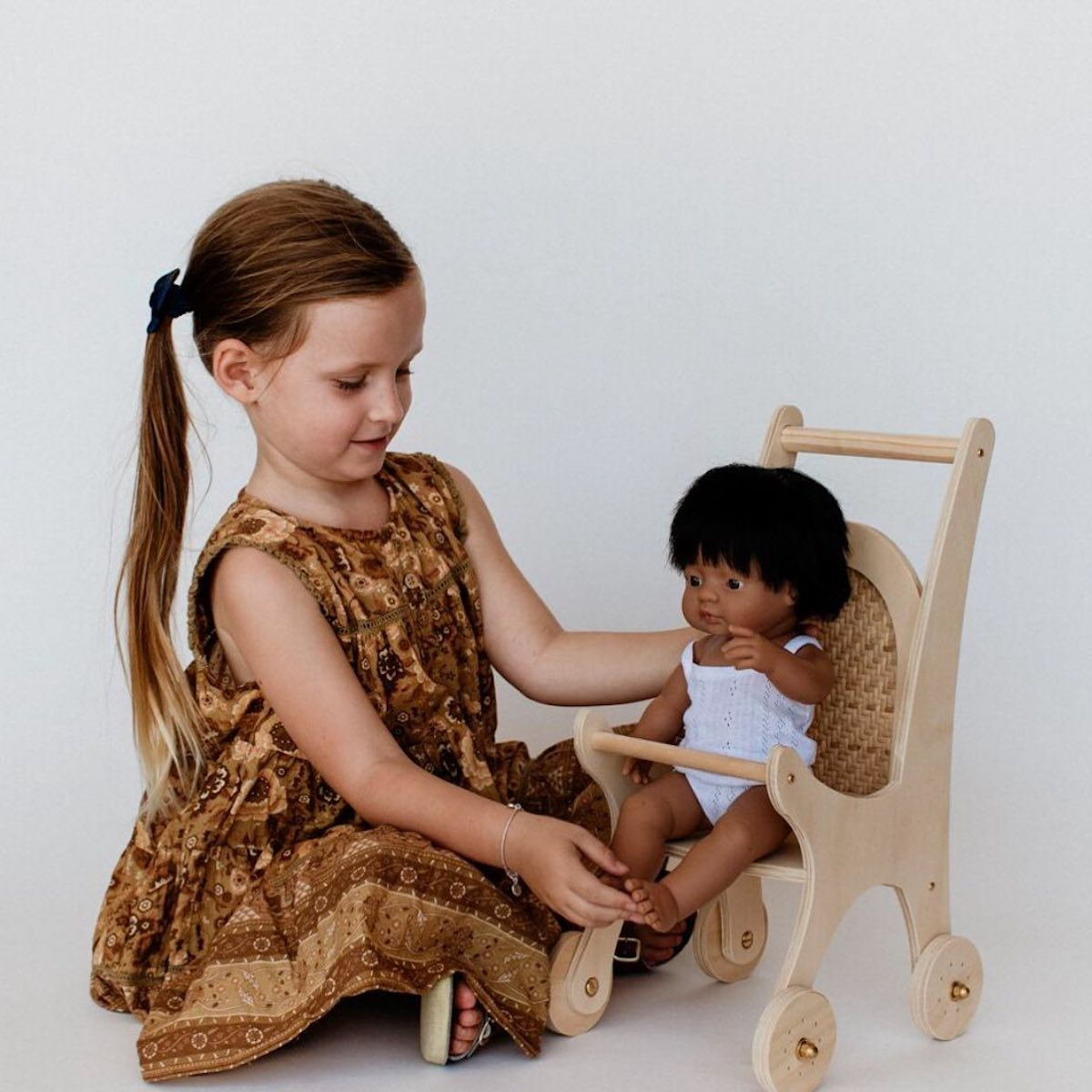Little girl wearing a brown dress playing with a Pretty in Pine doll in a wooden pram