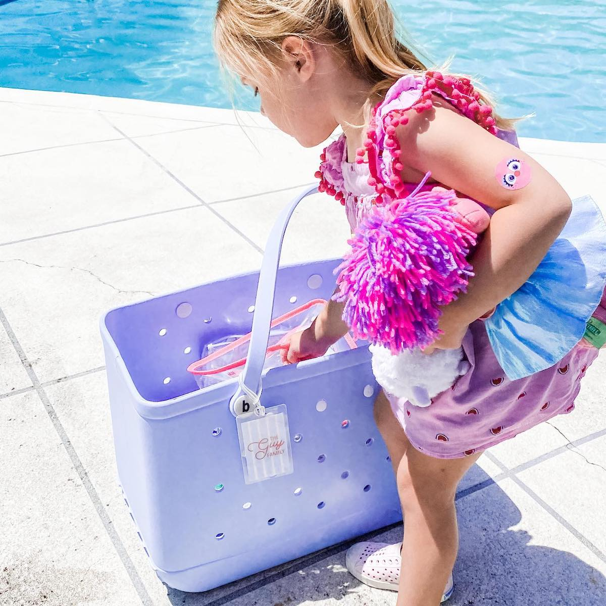 Little girl standing next to a pool reaching into a beach bag with a Hunny Bee Paperie bag tag attached