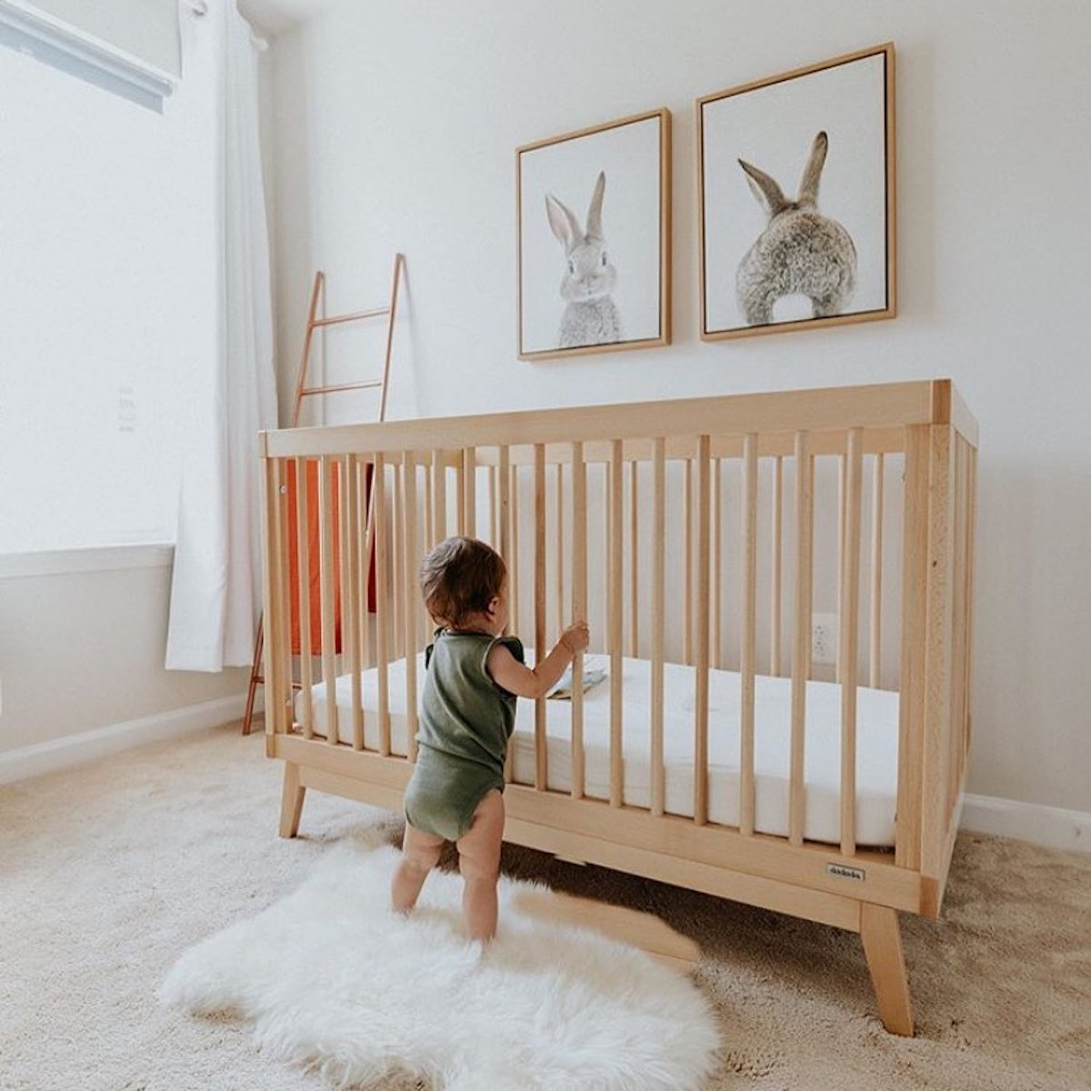 Toddler standing on a rug in their nursery holding on to a beech wood dadada crib