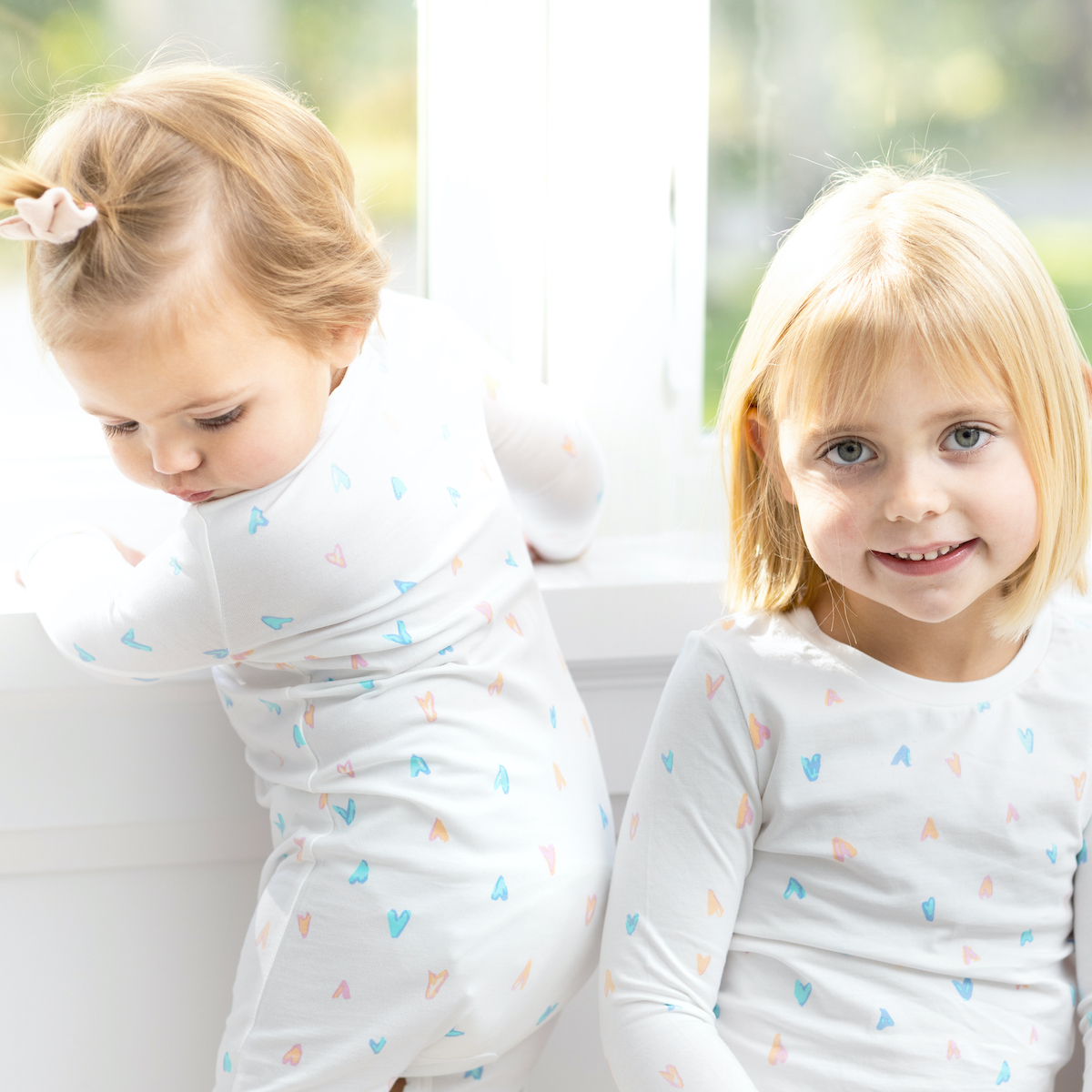 A child and infant wearing 12 | 12 pajamas on a porch