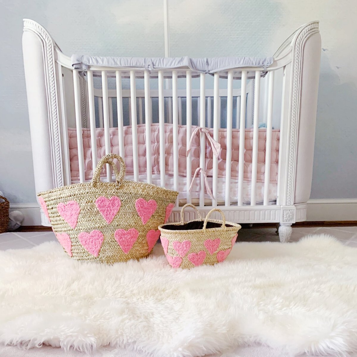 A white wooden crib with a pink mattress in a child's nursery with two Colores Collective Heart Totes