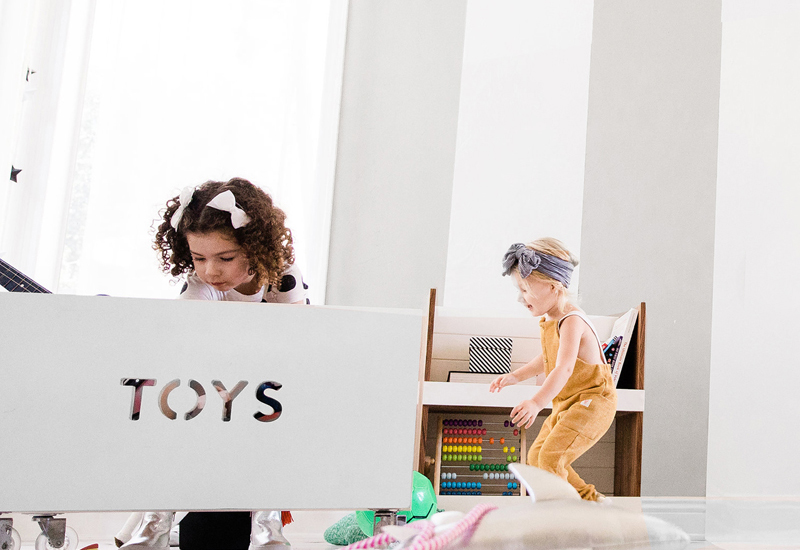 Kids storing their toys in a wooden toy box