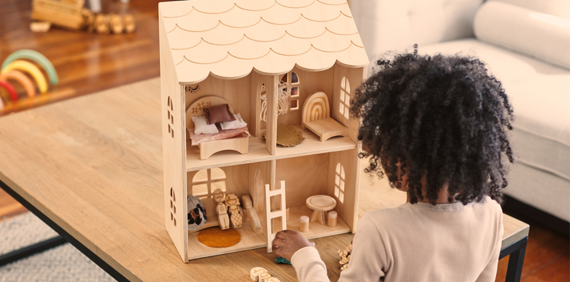 Black girl playing with non-toxic wooden dollhouse